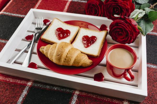 romantisches Frühstück zu zweit Tablett Kaffee mit Milch Croissants rote Rosen Toast mit Marmelade