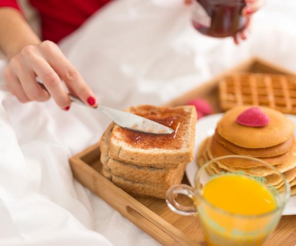 romantisches Frühstück zu zweit Toast mit Schokolade Kekse frisch gepresster Saft