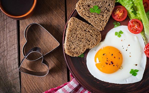 romantisches Frühstück zu zweit gesunde Ernährung Vollkornbrot Spiegelei in Herzform Tomate Salatblatt