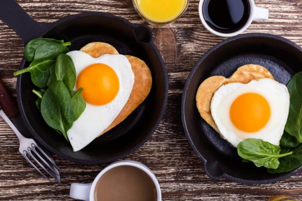romantisches Frühstück zu zweit pfannkuchen gebratene Eier in herzform Spinat