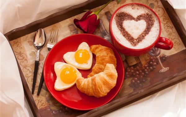 romantisches Frühstück zu zweit rotes Geschirr Cappuccino Herzform Croissants gebratene Eier in Herzform auf Tablett rote Rose