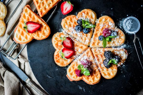 romantisches Frühstück zu zweit warme Herzwaffeln in Herzform mit Zucker und Beeren