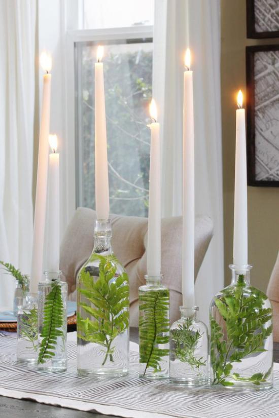 skandinavische Frühlingsdeko Glasvasen mit grünen Blättern darin brennende weiße Kerzen sehr elegantes Arrangement