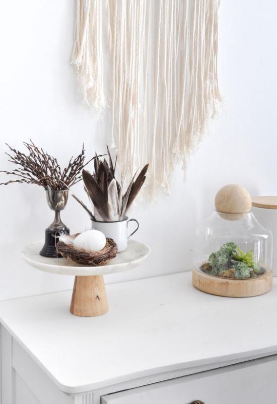 skandinavische Frühlingsdeko Makramee an der Wand Federn Zweige Nest ein weißes Ei Sukkulenten unter Glas