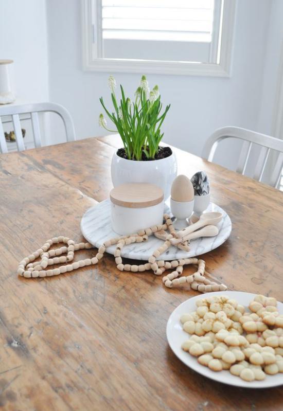 skandinavische Frühlingsdeko Tisch aus hellem Holz weiße Blumen im Topf andere Deko Artikel
