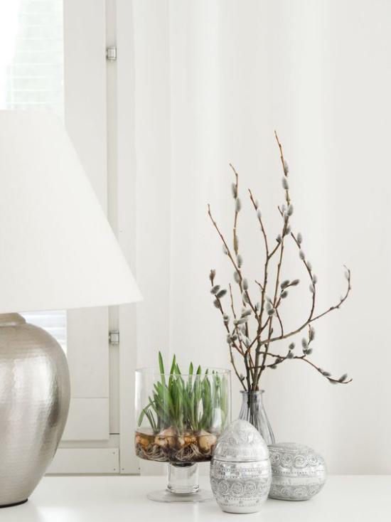 skandinavische Frühlingsdeko Tischdeko neben Tischlampe Eier Vase mit Zweigen Glasgefäß mit Frühlingsblumen