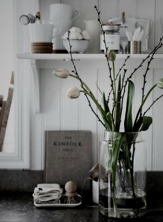 skandinavische Frühlingsdeko Vase aus Glas weiße Tulpen weitere Deko Artikel dunkelgrauer Hintergrund