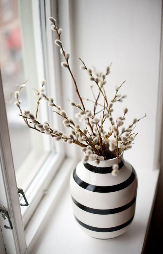 skandinavische Frühlingsdeko Vase blühende Zweige am Fenster platziert