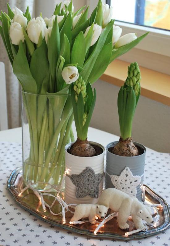 skandinavische Frühlingsdeko auf dem Esstisch weiße Tulpen Hyazinthen kleine Bärenfiguren