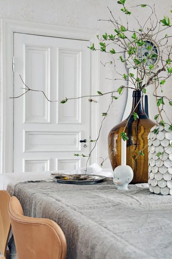 skandinavische Frühlingsdeko auf dem Tisch hohe Vase Zweige grüne Blätter einfach und schön
