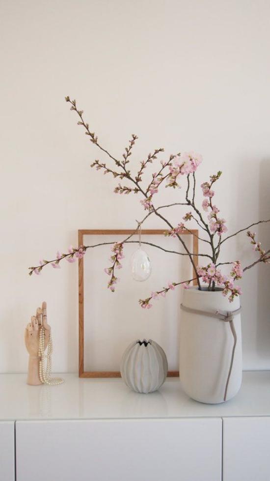 skandinavische Frühlingsdeko auf der Kommode elegantes Arrangement rosa Kirschblüten