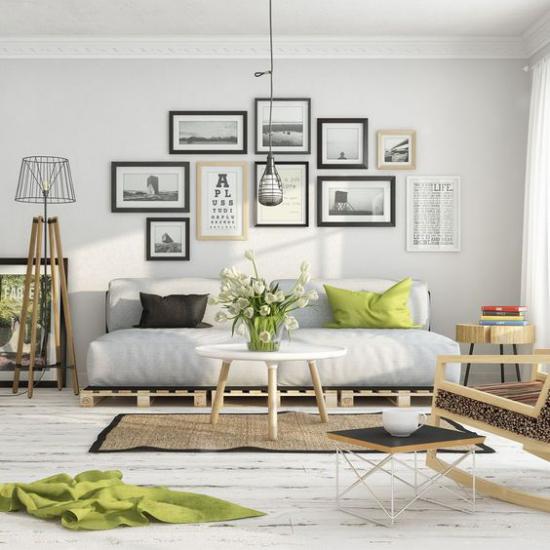 skandinavische Frühlingsdeko elegantes gemütliches Wohnzimmer in Grauweiß hellgrüne Decke Kissen als frische Akzente viele Wandbilder