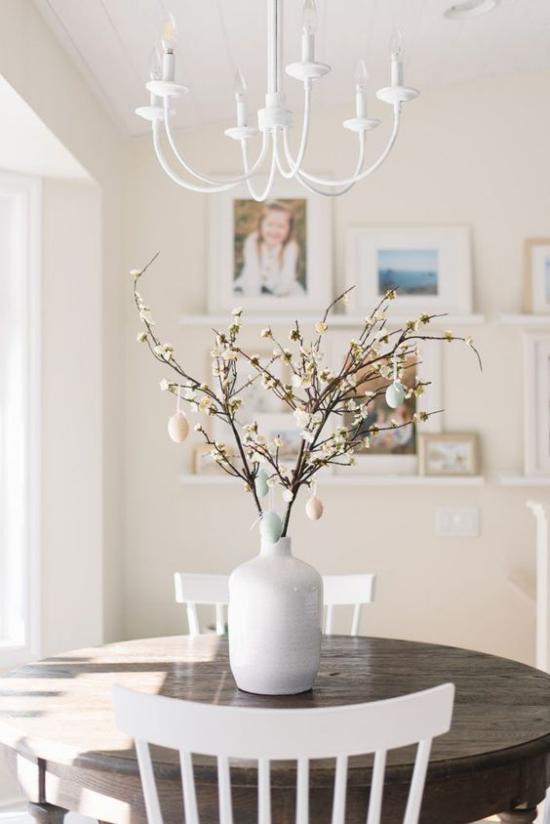 skandinavische Frühlingsdeko runder Esstisch Vase Zweige Eier in Pastellfarben helles sonniges Ambiente