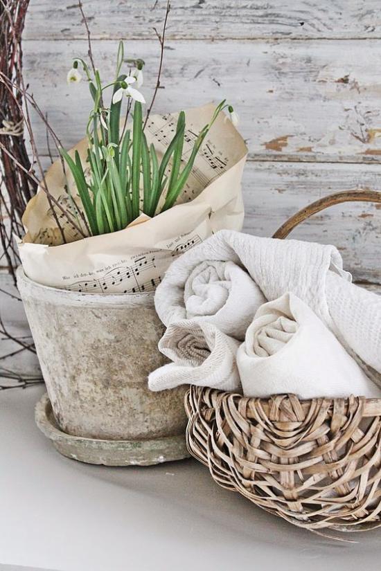 skandinavische Frühlingsdeko rustikales Arrangement alter Blumentopf weiße Schneeglöckchen Korb mit Tüchern