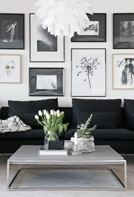 skandinavische Frühlingsdeko schönes Wohnzimmer elegante Möbel Wandbilder schwarze Couch niedriger Tisch weiße Tulpen