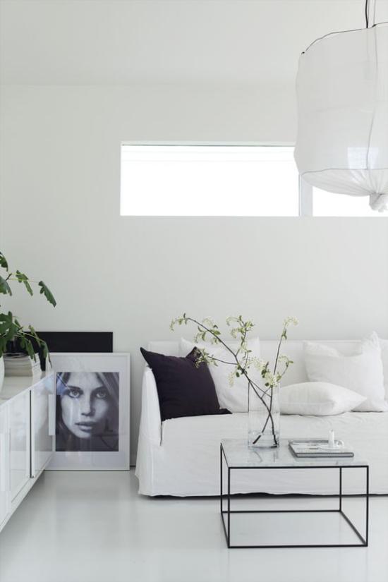 skandinavische Frühlingsdeko sehr elegantes Interieur weiße Möbel großes Bild Glastisch Glasvase Zweige