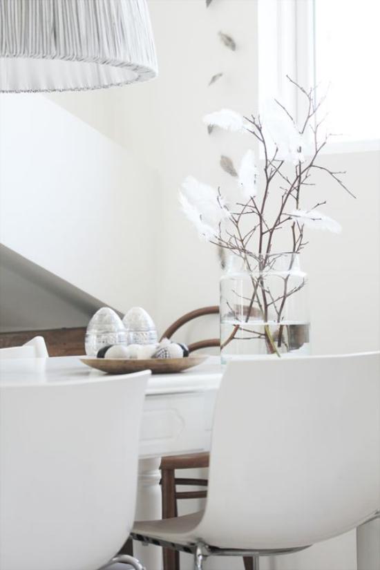 skandinavische Frühlingsdeko weißes Ambiente auf dem Tisch interessantes Arrangement Glasvase Zweige Federn Eier