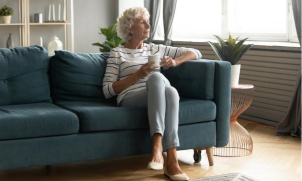 vitalisierende Tees beliebte Muntermacher gegen Frühjahrsmüdigkeit Frau auf der Couch trinkt Tee