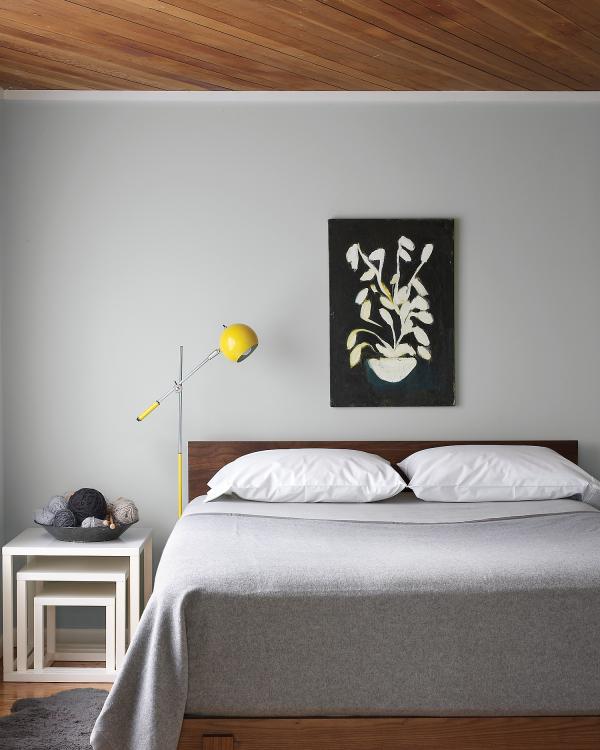 Aktuelle Wandfarben graues Schlafzimmer Hellgrau an der Wand Tagesdecke weiße Kissen kleines Highlight in Gelb Lampe