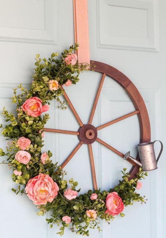 Frühlingskränze altes Rad geschmückt an der Haustür rustikaler Look viel Grün schöne Blüten