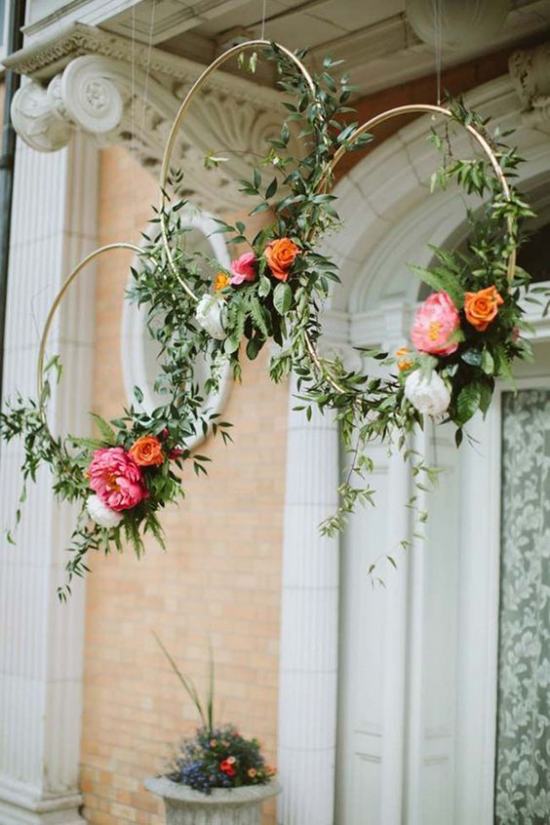 Frühlingskränze dünne Metallreifen vor der Haustür gehängt mit Blüten und Grün geschmückt ausgefallene Deko