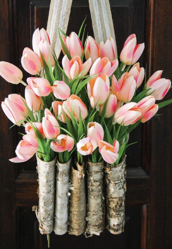 Frühlingskränze kleine Blumenbehälter aus Birkenrinde an der Haustür voller rosafarbener Tulpen