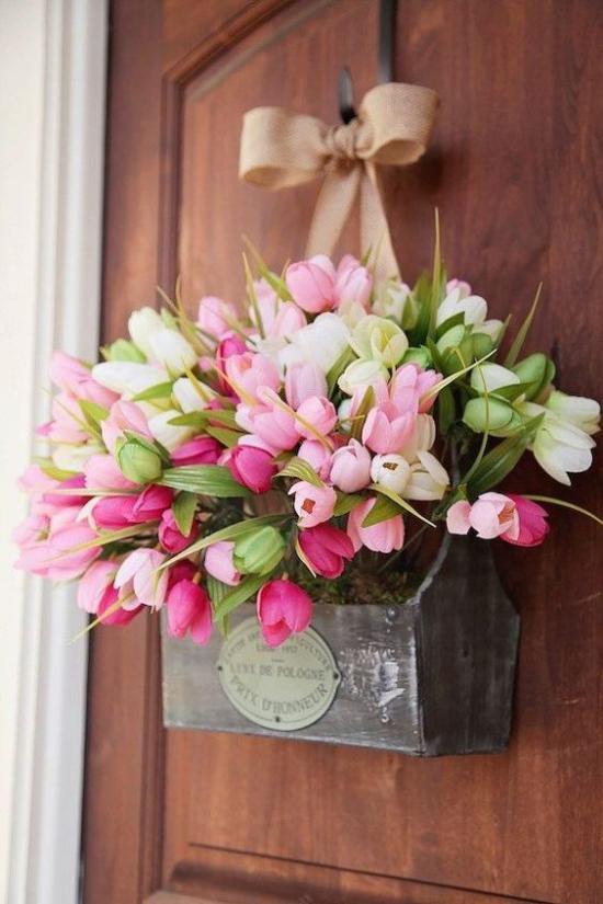 Frühlingskränze schöne rosa Tulpen im alten Holzkasten an der Haustür