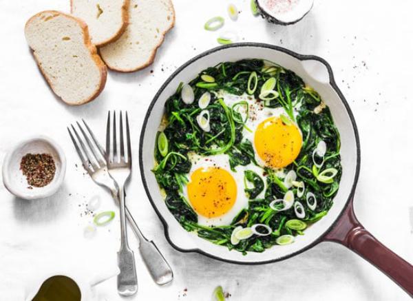 Gründonnerstag grüne Speisen traditionelle Rezepte in der Pfanne Spinat Frühlingszwiebeln in Scheiben geschnitten zwei Eier darauf