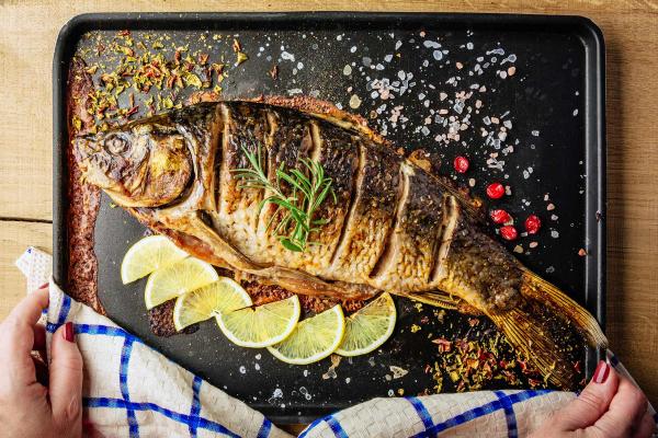 Karfreitag Fischtag Fisch auf dem Blech im Ofen gebraten mit Rosmarin garniert Zitronenscheiben