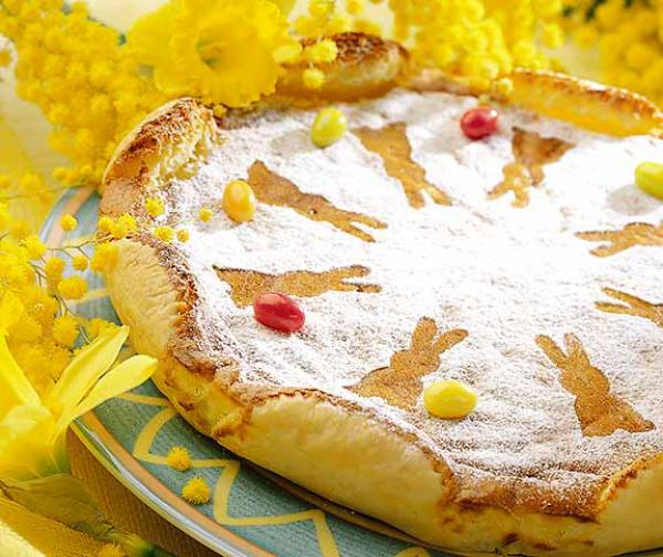 Ψήστε το κέικ του Πάσχα τον εαυτό σας Παγωτό ζάχαρης με πολύχρωμες καραμέλες στολίζουν κίτρινα νάρκισσους γύρω από