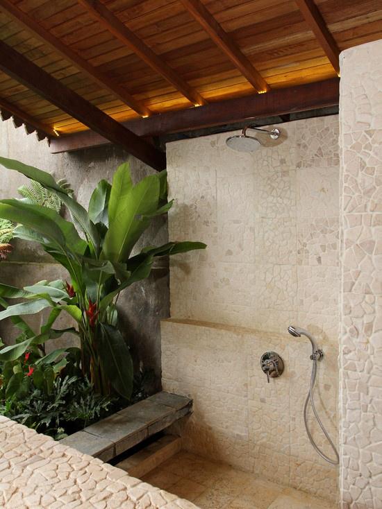 Tropische Deko im Bad üppige grüne Pflanzen große Blätter viel Naturstein Holz schönes Ambiente