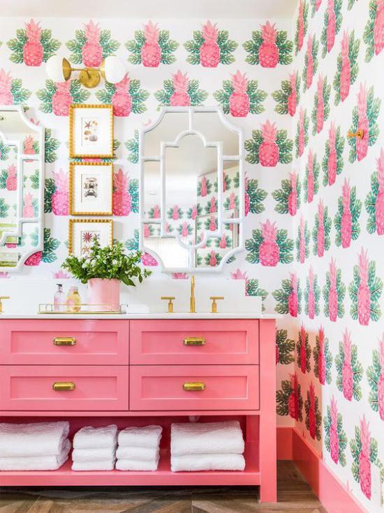 Tropische Deko im Bad Tapetenmuster Ananas Blätter exotischer Look Spiegel Bilder rosa Schrank weiße Badetücher