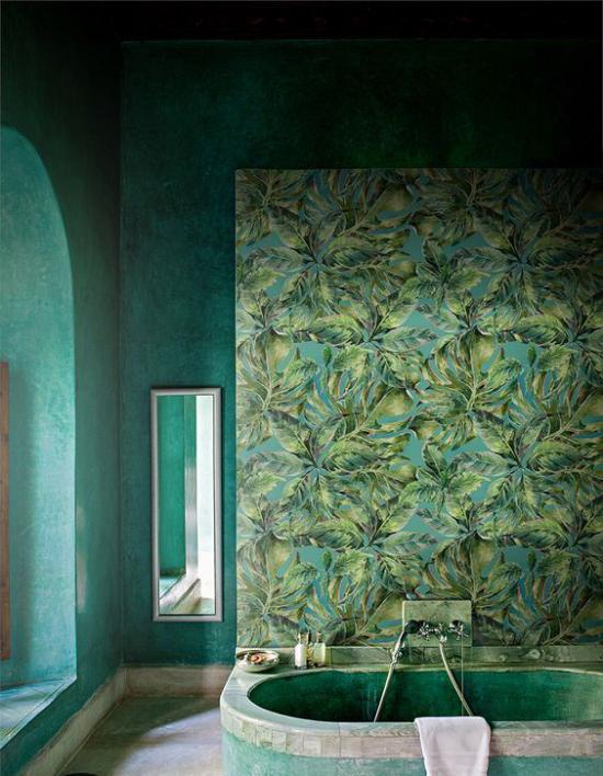 Tropische Deko im Bad grüne Wände Tapete exotische Blätter eingebaute Badewanne Wandspiegel im Hintergrund Fenster links