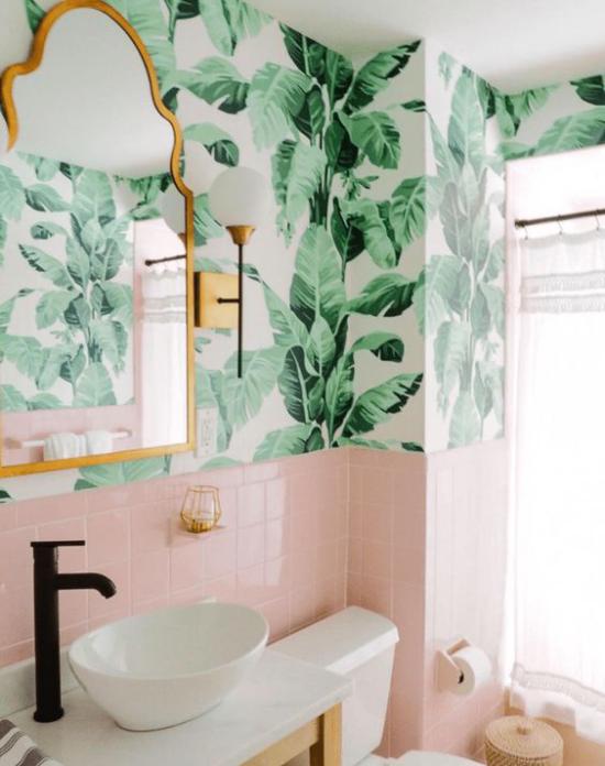 Tropische Deko im Bad helles einladendes Ambiente rosa Fliesen weißes Waschbecken tropische Muster Wandtapete Spiegel Wasserhahn schwarz