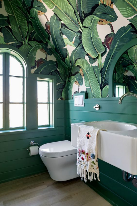 Tropische Deko im Bad schöne Tapete große Blätter weiße Badezimmermöbel WC Bodenfliesen links Fenster