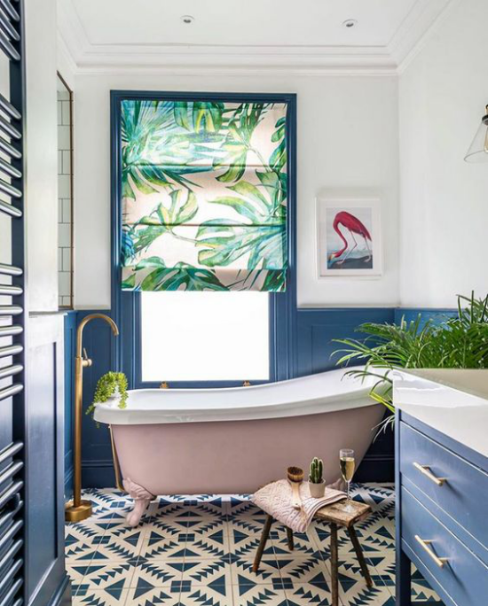 Tropische Deko im Bad viel Licht Fenster fein gemusterte Bodenfliesen freistehende Badewanne mit Löwenfüßen