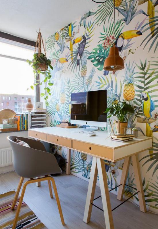 Tropische Deko im Home Office Arbeitsecke links großes Fenster Akzentwand tropische Muster Papageien Ananasse Gelb Blau Grün fröhlicher Farbmix