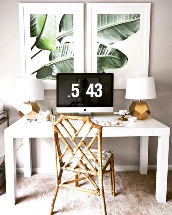 Tropische Deko im Home Office Naturmaterialien Holztisch Rattan-Sessel Uhr zwei Wandbilder tropische Blätter