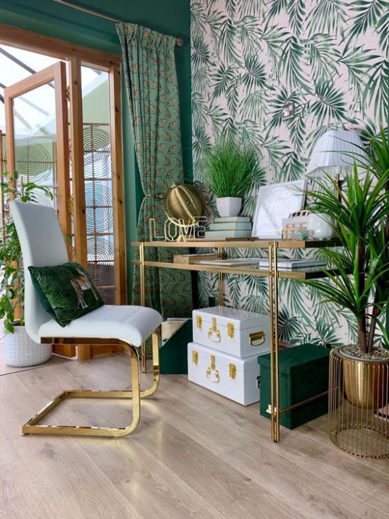 Tropische Deko im Home Office großer heller Raum grüne Farbe dominiert Schreibtisch Sessel Akzentwand Tapete große tropische Blätter grüne Topfpflanzen