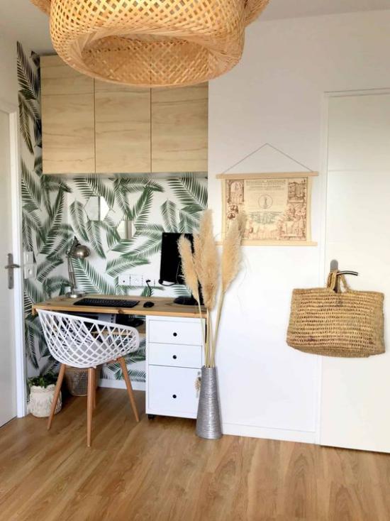Tropische Deko im Home Office kleine Arbeitsecke in der Nische Akzentwand tropische Blätter Naturmaterialien Rattan Ziergras Flechttasche an der Tür