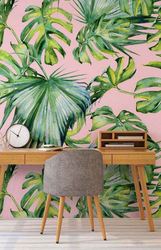 Tropische Deko im Home Office schöne Raumatmosphäre Schreibtisch aus Holz Bürosessel Uhr Akzentwand tropische Muster auf Tapete