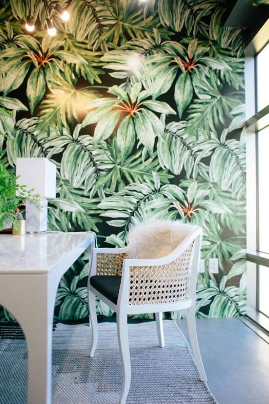 Tropische Deko im Home Office weiße Möbel Akzentwand große tropische Blätter auf Tapete schicke Beleuchtung viel Tageslicht