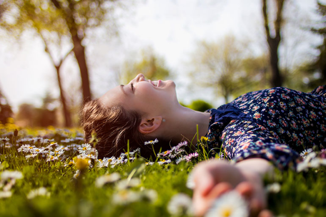 Weltfrauentag am 8.März junge Frau im Park liegt im Gras in der Sonne glücklich sein