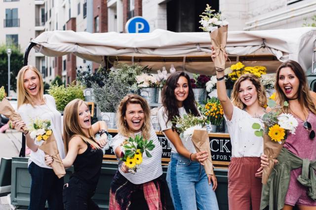 Weltfrauentag am 8.März junge Frauen mit Blumensträußen in der Hand feiern den 8. März