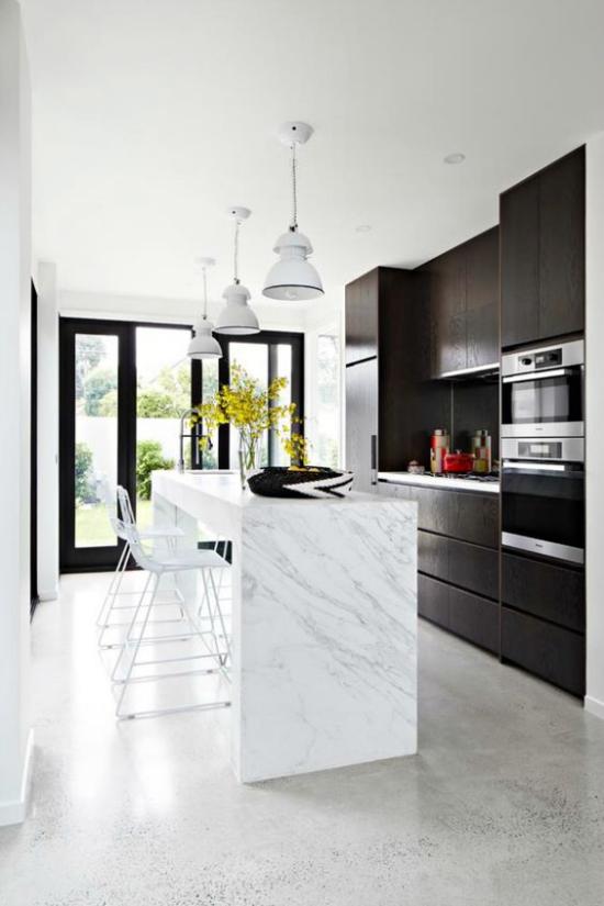 grauer Boden Beton moderne Küche weiße Kücheninsel schwarze Schränke Hängeleuchten