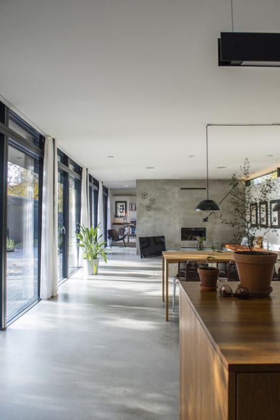 grauer Boden Betonboden minimalistischer offener Raum links deckenhohe Fenster viel Tageslicht