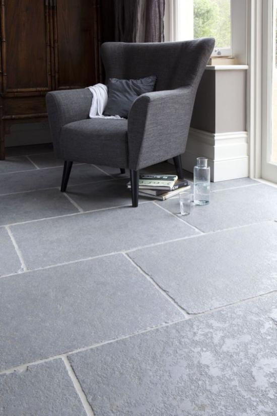 grauer Boden Steinplatten im Interieur eingesetzt dunkelgrauer Sessel natürlicher Look Robustheit in einem