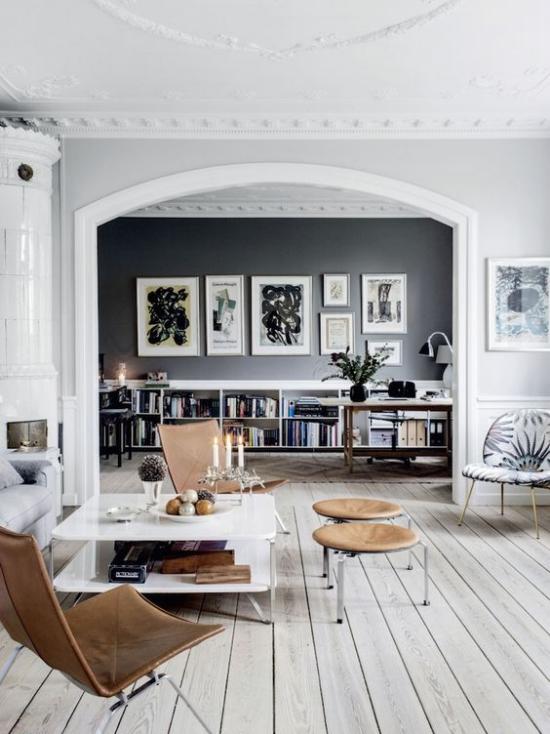 grauer Boden Wohnzimmer offener raum niedrige Möbel Akzente in Schokoladenbraun Hocker Stühle schöne Wandbilder