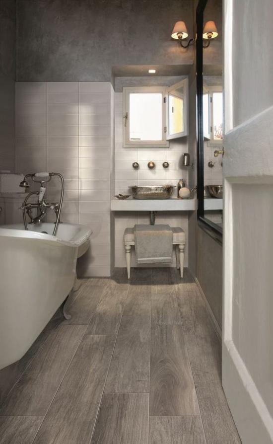 grauer Boden dunkles Badezimmer links Badewanne kleines Fenster Waschtisch