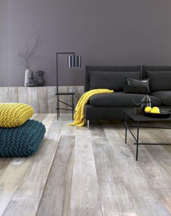 grauer Boden gelbe Akzente Wohnzimmer Blickfang schwarzes Sofa